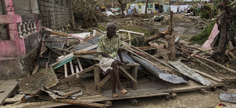A man sits on a pile of rubble caused by Hurrican Matthew