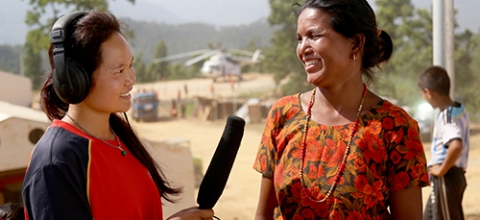 A journalist in Nepal interviews a woman after the earthquake