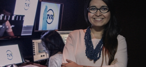 A woman stands in the foreground of a TV station, another woman sits behind her working on a laptop.
