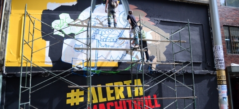 "Men are painting on the outside wall of a building. In large letters below them, are the words ""#Alerta Machitroll."""