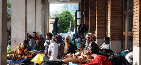 A group of women and children sit outside a brick building