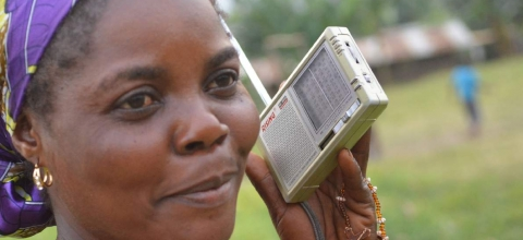 A woman holds a transistor radio up to her ear.